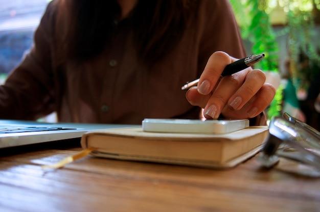 Usinessman analyse les tableaux d'investissement et appuie sur les boutons de la calculatrice sur les documents. concept comptable.