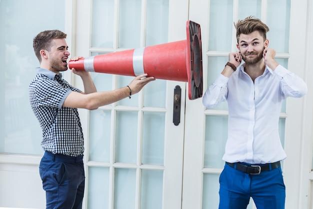 Usinessman crier mégaphone à son ami