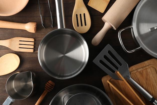 Ustensile de cuisine différent sur fond en bois, vue de dessus.