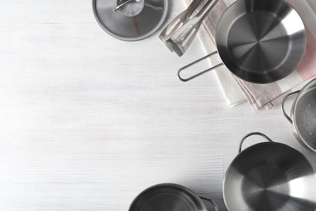 Ustensile de cuisine sur fond en bois blanc, vue de dessus.
