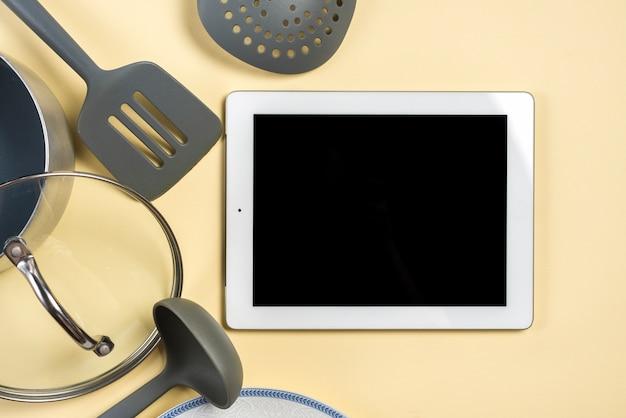 Ustensile; spatule; louche et tablette numérique écran noir sur fond beige