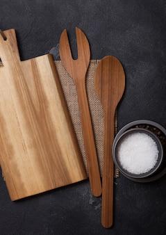 Ustensiles en bois de cuisine vintage avec planche à découper sur table en pierre noire. vue de dessus.