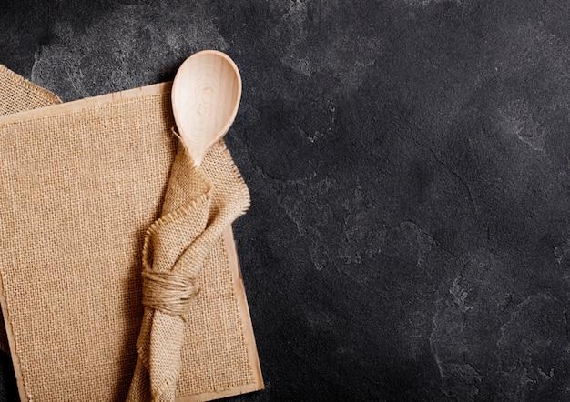 Ustensiles en bois de cuisine vintage avec planche de lin sur table en pierre. vue de dessus.