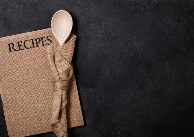 Ustensiles en bois de cuisine vintage avec planche de recettes de lin sur table en pierre. vue de dessus.