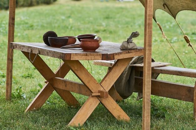 Ustensiles en bois médiévaux placés sur une grande table en bois