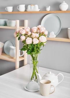 Ustensiles, bouquet de roses et tasses sur étagère. plats dans le placard de la cuisine.