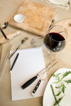 Ustensiles, carnet et verre de vin