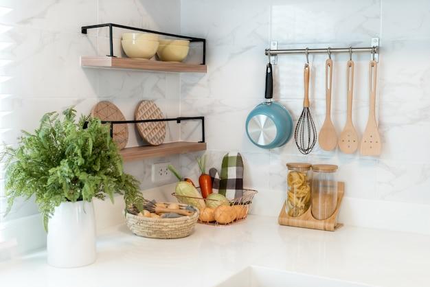 Ustensiles de cuisine en bois, accessoires de chef. cuisine en cuivre suspendue avec mur de carreaux blancs.
