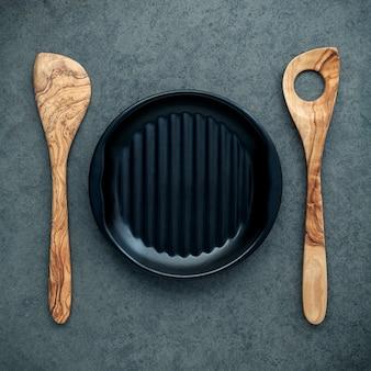 Ustensiles de cuisine en bois, cuillères en bois, spatule et plaque noire sur fond sombre.