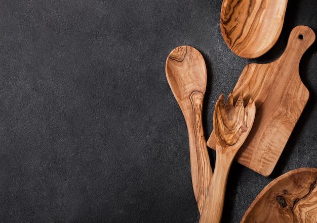 Ustensiles de cuisine en bois d'olivier avec planche à découper et bol sur table en pierre. vue de dessus.