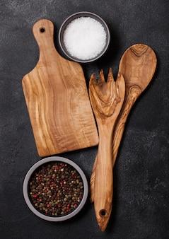 Ustensiles de cuisine en bois d'olivier avec planche à découper sur table en pierre. vue de dessus.
