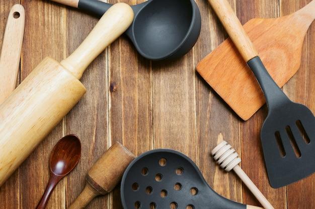 Ustensiles de cuisine en bois et silicone sur la planche à découper. louche, cuillère, spatule, rouleau à pâtisserie, presse-purée et cuillère en bois avec espace copie. outils de cuisine.