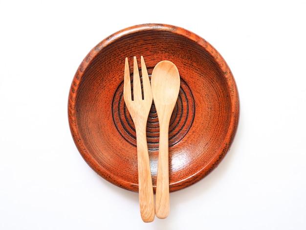 Ustensiles de cuisine avec une cuillère et une fourchette en bois sur une assiette ronde brune, un plat et des couverts