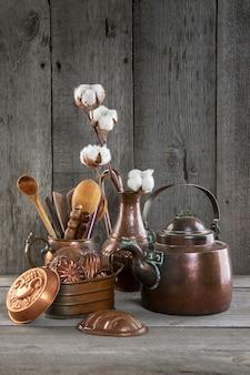 Ustensiles de cuisine en cuivre vintage sur un fond gris en bois.