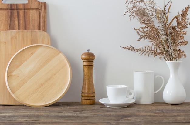 Ustensiles de cuisine sur étagère en bois dans la cuisine blanche