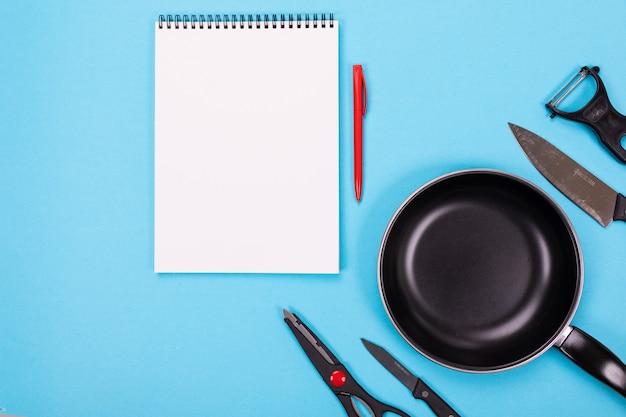 Ustensiles de cuisine et feuille de papier propre sur bleu