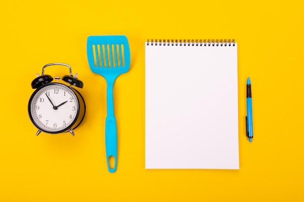 Ustensiles de cuisine et feuille de papier propre isolé sur fond jaune