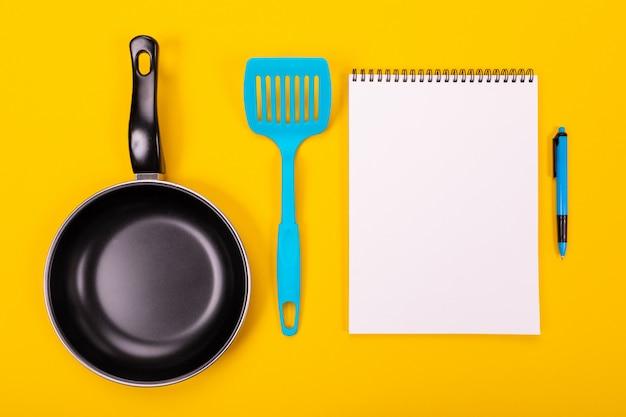 Ustensiles de cuisine et feuille de papier propre isolé jaune