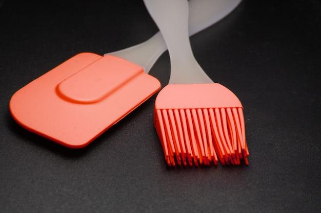 Ustensiles de cuisine sur fond noir. spatule en silicone, brosse de près