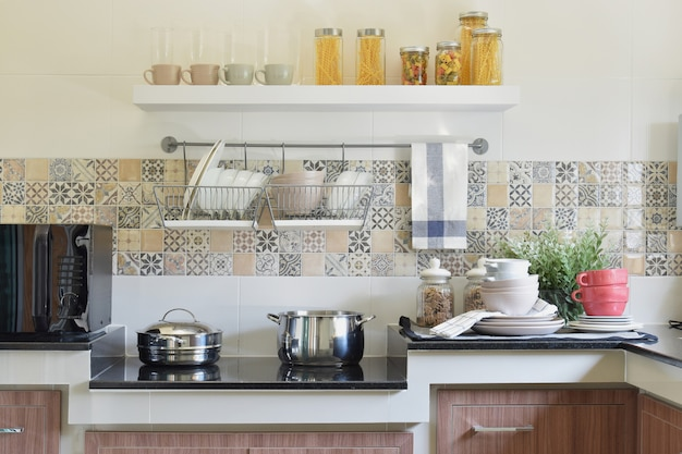 Ustensiles de cuisine modernes en céramique et ustensiles sur le comptoir en granit noir