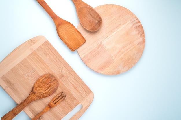 Ustensiles de cuisine et planches à découper sur fond clair.