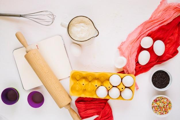 Ustensiles de cuisine à proximité du bloc-notes et des ingrédients