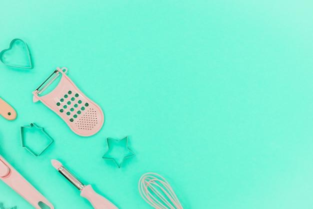 Ustensiles de cuisine rose sur fond néo menthe. forme de cuisson plus grande, au fouet et au fer. copyspace vue de dessus