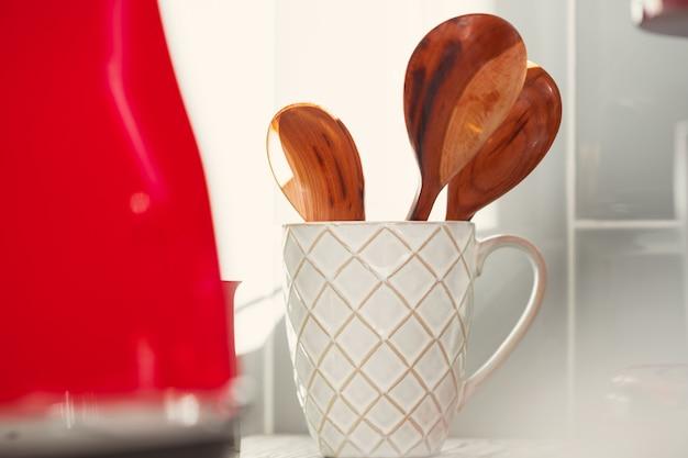 Ustensiles de cuisine en tasse sur table close up