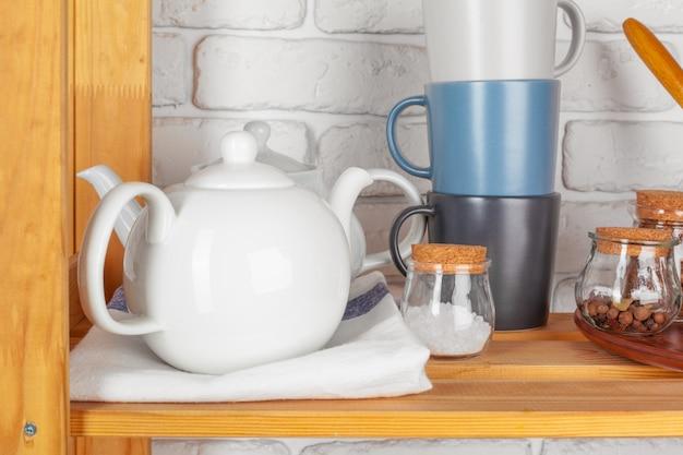 Ustensiles de cuisine et vaisselle sur une étagère en bois
