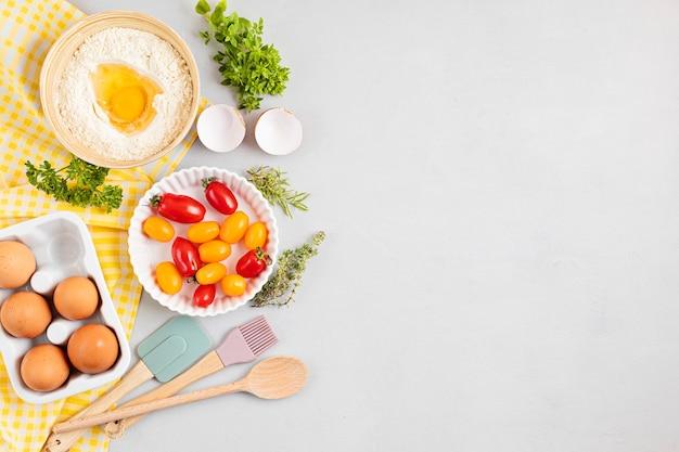 Ustensiles de cuisson et ingrédients de cuisson pour tartes, pâtes et pâtisseries. mise à plat avec des œufs, de la farine, des tomates, des herbes.