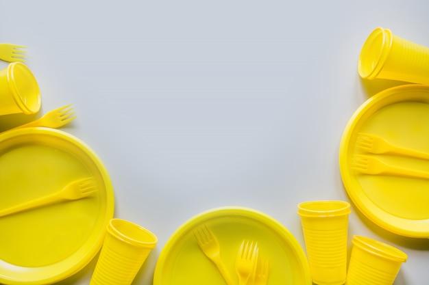 Ustensiles jaunes de pique-nique à usage unique, assiettes, tasses, fourchettes sur fond gris.