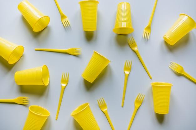 Ustensiles jetables de pique-nique jaune sur gris. lay plat.