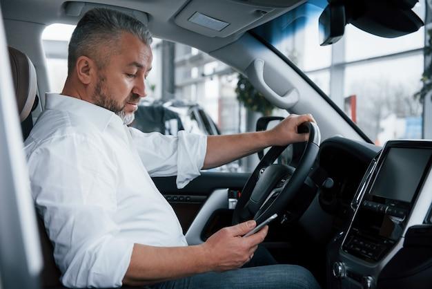 En utilisant un téléphone portable. homme d'affaires est assis dans la voiture moderne et a des offres