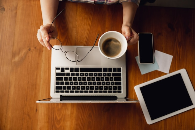 Utilisation d'appareils. gros plan des mains des femmes de race blanche, travaillant au bureau. concept d'entreprise, de finance, d'emploi, d'achat en ligne ou de vente. espace de copie. indépendant de l'éducation, de la communication.