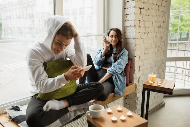 Utilisation d'appareils. verrouillage de la quarantaine, concept de séjour à la maison - jeune beau couple caucasien profitant d'un nouveau style de vie pendant l'urgence sanitaire mondiale du coronavirus. bonheur, convivialité, santé.