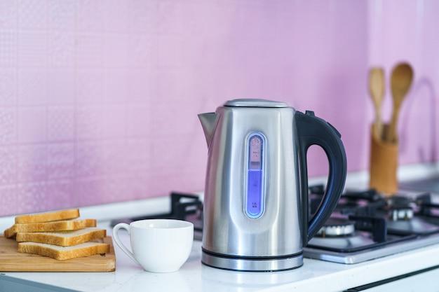 Utilisation d'une bouilloire électrique pour préparer du thé à la maison dans la cuisine
