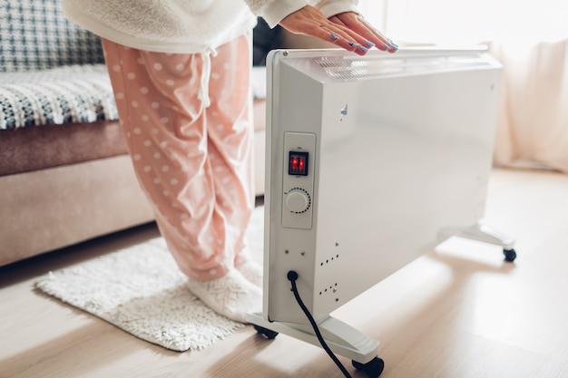 Utilisation de chauffage à la maison en hiver. femme se réchauffant les mains. saison de chauffage.