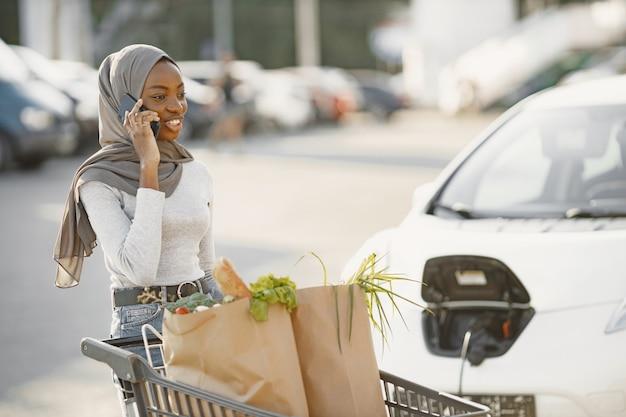 Utilisation du smartphone en attendant. femme d'origine africaine sur la station de recharge de voitures électriques pendant la journée. véhicule tout neuf.