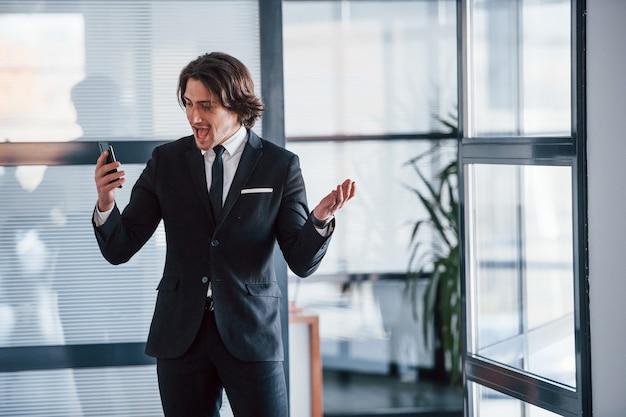 Utilisation du téléphone. portrait de beau jeune homme d'affaires en costume noir et cravate.