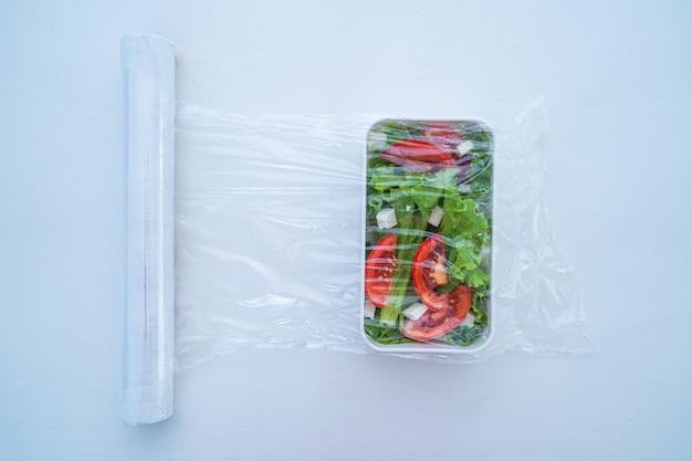 Utilisation d'un film plastique en polyéthylène alimentaire pour le stockage des aliments dans le réfrigérateur à la maison. vue de dessus. protection alimentaire