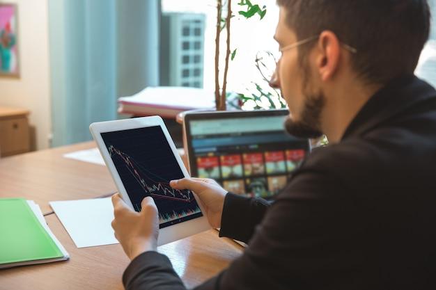 Utilisation de gadgets. entrepreneur caucasien, homme d'affaires, gestionnaire travaillant concentré au bureau. il a l'air sérieux et occupé, en tenue classique. concept de travail, finance, entreprise, succès, leadership.