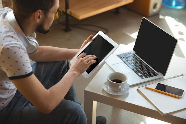 Utilisation de gadgets. homme travaillant à domicile pendant le coronavirus ou la quarantaine covid-19, concept de bureau à distance. jeune homme d'affaires, gestionnaire effectuant des tâches avec un smartphone, un ordinateur, a une conférence en ligne, une réunion.