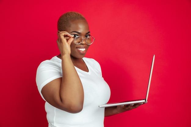 Utilisation d'un ordinateur portable. portrait de jeune femme afro-américaine sur fond rouge. beau modèle féminin en chemise. concept d'émotions humaines, expression faciale, ventes, publicité, inclusion, bureau. espace de copie.