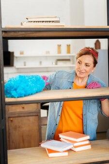 Utilisation d'un outil moelleux. femme attentive positive portant une tenue lumineuse et des gants roses tout en nettoyant toute la maison