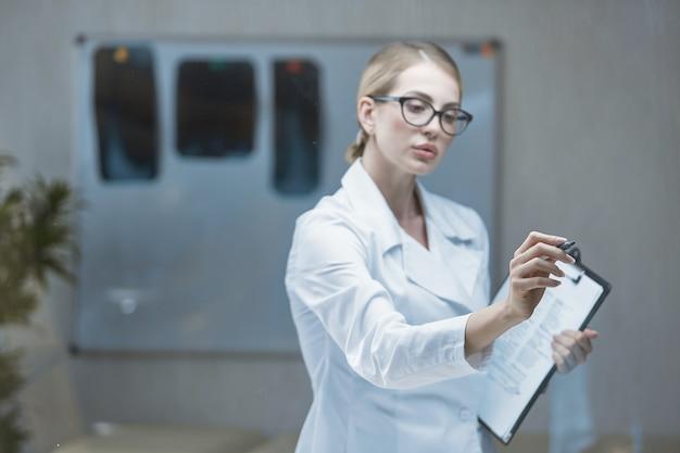 L'utilisation des technologies modernes par une femme médecin, travaillant sur un écran de verre