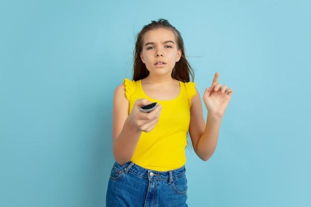 Utilisation de la télécommande du téléviseur. portrait de l'adolescente caucasienne isolé sur bleu