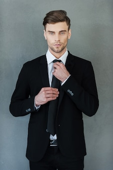 Utilisé pour avoir l'air parfait. beau jeune homme d'affaires ajustant sa cravate et regardant la caméra