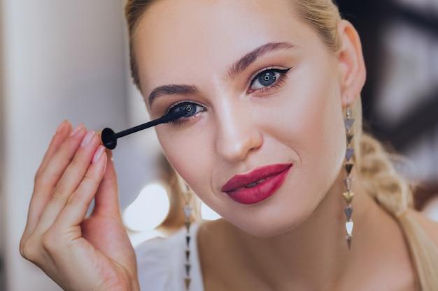 Utiliser du mascara. femme aux cheveux blonds avec des lèvres rouges à l'aide de son mascara tout en finissant son maquillage du soir