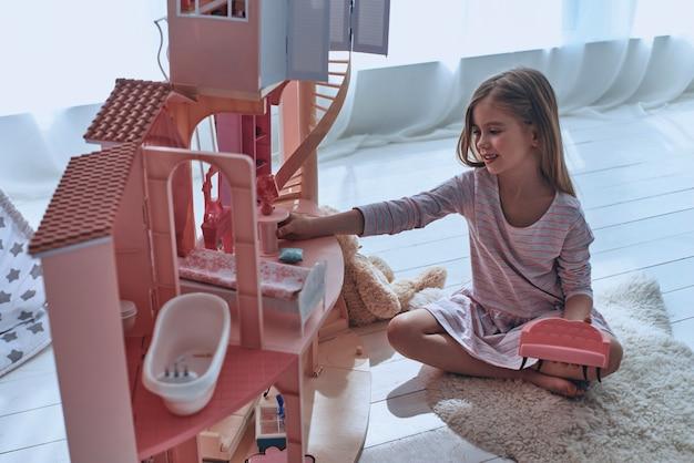 Utiliser la fantaisie pour jouer. petite fille mignonne jouant avec une maison de poupée alors qu'elle était assise sur le sol dans la chambre