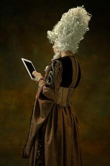 Utiliser la tablette pour être en ligne. portrait de jeune femme médiévale en vêtements vintage marron sur un mur sombre. modèle féminin en tant que duchesse, personne royale. concept de comparaison des époques, moderne, mode.